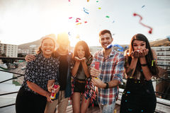 Best friends on a rooftop party. Group of friends hanging out together and blowing confetti on rooftop party royalty free stock images