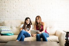 Doing some online shopping. Best friends and roomies doing some online shopping with a tablet computer and a credit card. Plenty of copy space Royalty Free Stock Images