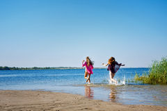 Best friends running to swim in river. Stock Photography