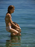Best friends at sea. Two cute  young sisters - children , happy and smiling standing in the sea (piggy back) - spend summer holidays in the clear Adriatic Sea in Royalty Free Stock Photo