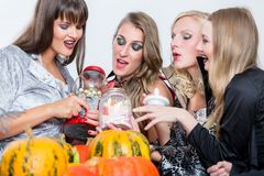 Best friends sharing candies while celebrating Halloween at cost Stock Image
