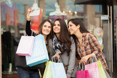 Best friends shopping and taking a selfie. Group of cute female friends doing some shopping at a mall and taking a selfie with a smartphone Stock Image