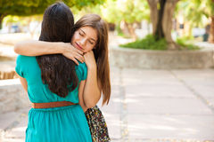 Best friends showing some love. Beautiful teenage friends hugging each other with their eyes closed. Lots of copy space stock photography
