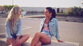 Best friends or sisters sitting and talking showing lovely relationship. They look happy stock video footage