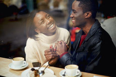 Best friends smiling sitting in cafe. Laughing young couple in cafe, having a great time together, view through cafe window, romantic couple having fun together Royalty Free Stock Photography