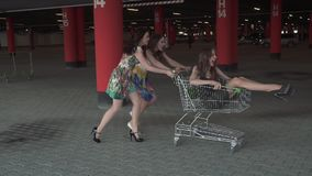 Best friends spend time together and have fun. friend racing grocery carts in the Parking lot. young people enjoying stock footage