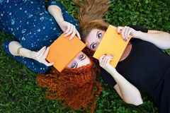 Best friends students hiding faces behind notebooks. Young cheerful girlfriends lie on the lawn in the city park. Best friends. Lovely girl students hiding Stock Photos