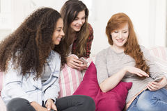 Best friends surfing the net together. Three energetic girls sitting on a sofa and looking at something on a mobile phone Stock Photos