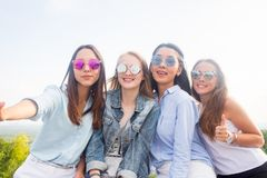 Best friends take selfies while walking in the Park. Four beautiful women wearing sunglasses are having a good day royalty free stock photo