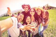 Best friends taking selfie at countryside picnic. Happy friendship concept and fun with young people and new technology trends - Vintage filter look with