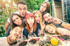 Best friends taking selfie at reatsurant drinking wine. Best friends taking selfie outdoor with back lighting - Happy youth concept with young people having fun Stock Image