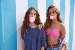 Best friends teen girls group bubble gum. In a summer blue stripes background royalty free stock photo