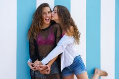 Best friends teen girls happy in summer beach. Best friends teen girls happy kiss in a summer blue stripes background Royalty Free Stock Photography