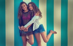 Best friends teen girls happy in summer beach. Best friends teen girls happy hug in a summer blue stripes background filtered image Royalty Free Stock Photo