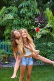Best friends teen girls piggyback on backyard. Garden happy smiling Royalty Free Stock Photography