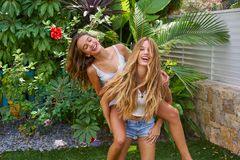 Best friends teen girls piggyback on backyard. Garden happy smiling Stock Photo