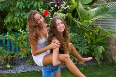 Best friends teen girls piggyback on backyard. Garden happy smiling Stock Photos