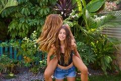 Best friends teen girls piggyback on backyard. Garden happy smiling Royalty Free Stock Photo