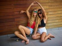 Best friends teen girls on skate having fun. Best friends teen girls on skate heart shape hands fingers smiling having fun royalty free stock photography