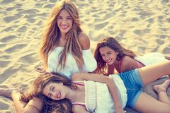 Best friends teen girls together on beach sunset. Best friends teen girls together relaxed on a beach sand at sunset Stock Images