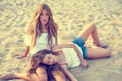 Best friends teen girls together on beach sunset. Best friends teen girls together relaxed on a beach sand at sunset Stock Photos
