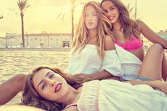Best friends teen girls together on beach sunset. Best friends teen girls together relaxed on a beach sand at sunset Stock Photo