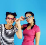 Best friends teenage school girls together having fun, posing emotional on blue background, besties happy smiling. Lifestyle people concept close up Stock Photo