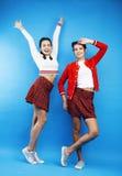 Best friends teenage school girls together having fun, posing emotional on blue background, besties happy smiling Royalty Free Stock Images