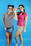 Best friends teenage school girls together having fun, posing emotional on blue background, besties happy smiling Royalty Free Stock Photos