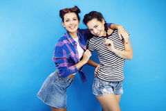 Best friends teenage school girls together having fun, posing emotional on blue background, besties happy smiling Royalty Free Stock Photos