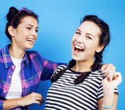 Best friends teenage school girls together having fun, posing emotional on blue background, besties happy smiling Stock Photos