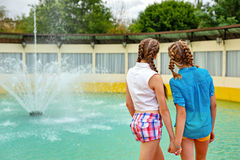 Best friends teenagers holding hands. Best friends teenagers holding hands at the fountain in summer park. Girls dressed in shorts and a shirt. On summer Stock Photo