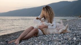 Best friends tender moment. Young curly girl holding her border collie dog like a baby. Pretty woman relaxing at the