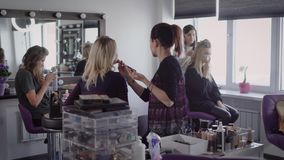 Best friends together came to a beauty salon to make a beautiful hair and makeup before a cool party. Girl sits on a stock video footage