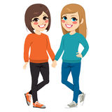 Best Friends Together. Cute young teenager best friends girls together holding hands standing isolated on white background Stock Photo