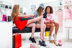 Best friends trying on different shoes talking sitting on a bench in a trendy fashion clothing store.  Royalty Free Stock Photography