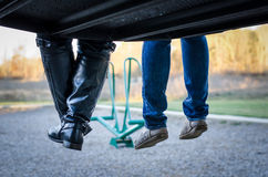 Best Friends. Two women sit together with their feet hanging over a childs playground Stock Photos