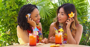Best friends on vacation listening to sea shells and drinking cocktails. Outdoors Royalty Free Stock Photo