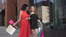 Best friends walking down the street with shopping bags. two beautiful young girls, a blonde and a brunette on the. Portrait of a young girl with a shopaholic stock video footage