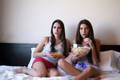 Best friends watching tv or a movie in bed Stock Images