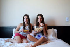 Best friends watching tv or a movie in bed Royalty Free Stock Photography