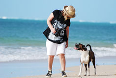 Best friends-Woman & pet dog walking on beach. Enjoying a holiday together, a middle-aged woman with her pet pure bred Boxer dog on the beautiful white sandy royalty free stock image