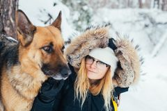 Portrait of young woman in winter coat with dog. Best friends, young blond woman in winter jacket and hat, stands next to her pet friend a big german shepherd Royalty Free Stock Photo