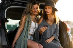 Best friens watching something on the phone. Two friends sitting in the trunk of a car while watching something on the phone Royalty Free Stock Image