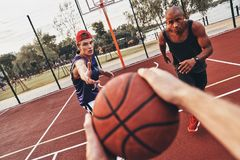 Best game ever. Close up of men holding ball while playing basketball with friends outdoors royalty free stock photography