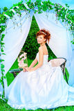 Best girl. Beautiful bride with chaming red hair sitting under the wedding arch. Wedding dress and accessories. Wedding decoration Stock Photography