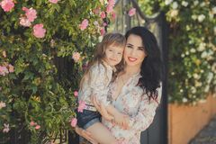 Best girlfriends adorable mother with dark black hairs and cute baby daughter with blond hairs and pink cheeks posing sit for toge royalty free stock image
