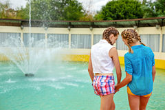 Best girlfriends holding hands. Best friends holding hands at the fountain in summer park. Girls dressed in shorts and a shirt. On summer vacation. The concept Royalty Free Stock Photos