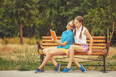 Best girlfriends are reading book while sitting on bench. Stock Photography