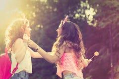 Best girlfriends share lollipops. Sunset. Stock Image